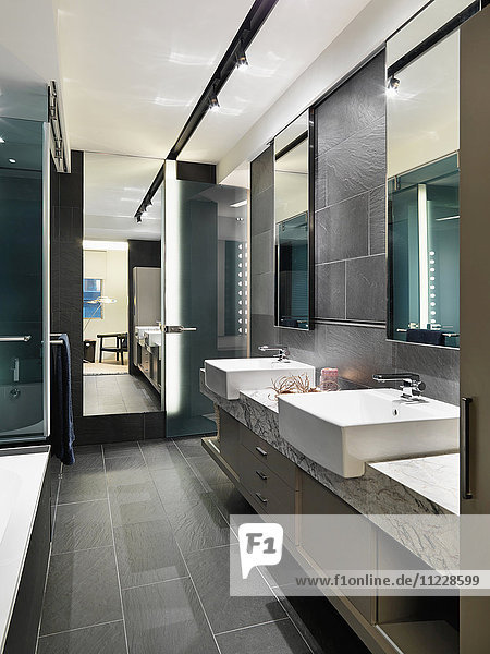 Slate tile floor and walls in modern bathroom