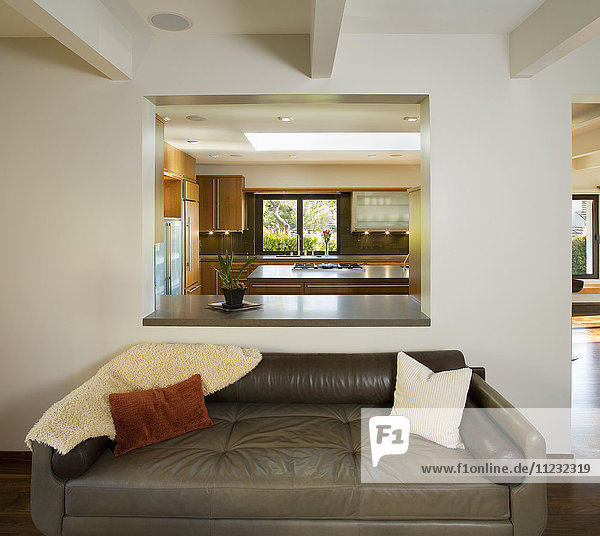 Leather Sofa in Modern Living Room with Cutout to Kitchen