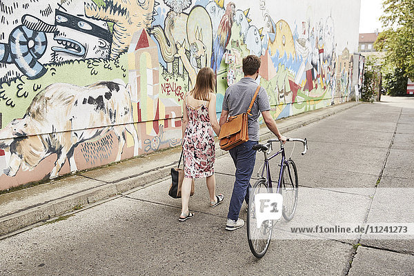 Couple with bicycle passing wall with graffiti