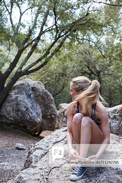 Frau sitzt auf Felsen und schnürt Schuhbänder