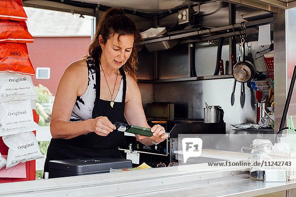 Woman using smartphone card reader for payment at food stall trailer