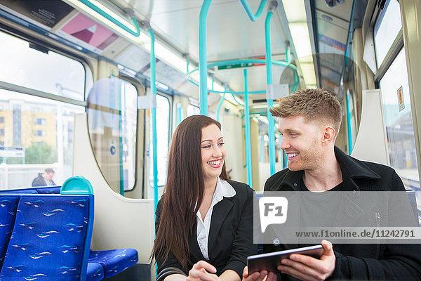 Geschäftsfrau und Geschäftsmann mit digitalem Tablet im Docklands Light Railway-Zug  London