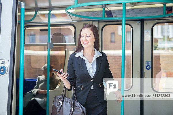 Businesswoman travelling in Docklands Light Railway train  London