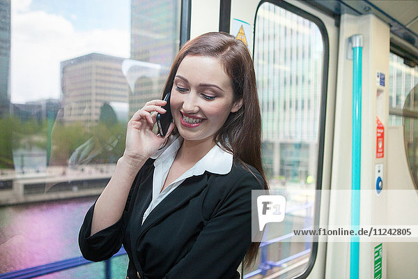 Geschäftsfrau benutzt Mobiltelefon im Docklands Light Railway-Zug  London