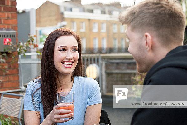 Junges Paar beim Plaudern auf der Terrasse, Junges Paar beim Plaudern auf der Terrasse