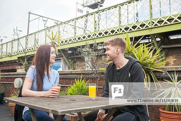 Junges Paar beim Plaudern auf der Terrasse