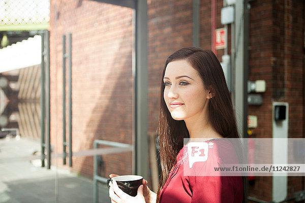 Geschäftsfrau beim Kaffeetrinken im Café