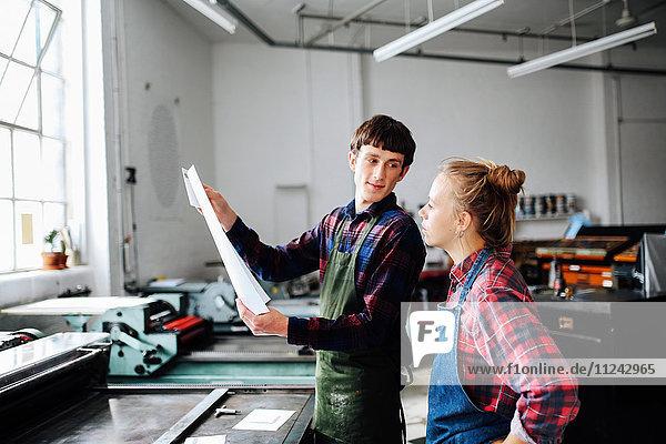 Junge Kunsthandwerker und Kunsthandwerkerinnen schauen sich Drucke in einem Buchkunst-Workshop an