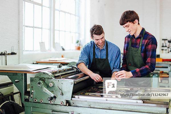 Zwei junge Männer arbeiten an einer Buchdruckmaschine in einem Buchkunst-Workshop