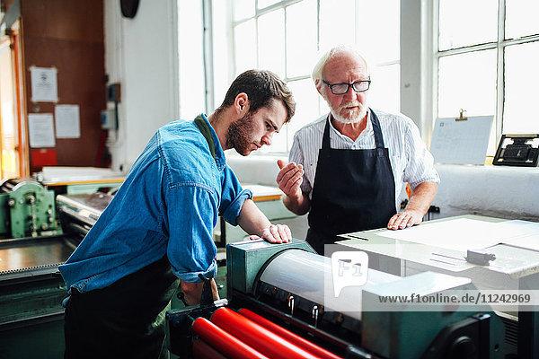 Leitender Handwerker/Techniker beaufsichtigt jungen Mann an Buchdruckmaschine in Buchkunstwerkstatt