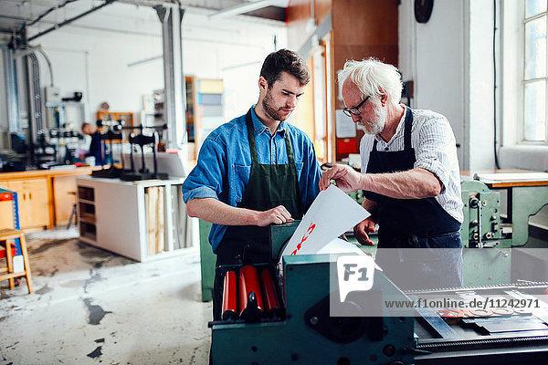 Senior craftsman/technician supervising young man on letterpress machine in book arts workshop