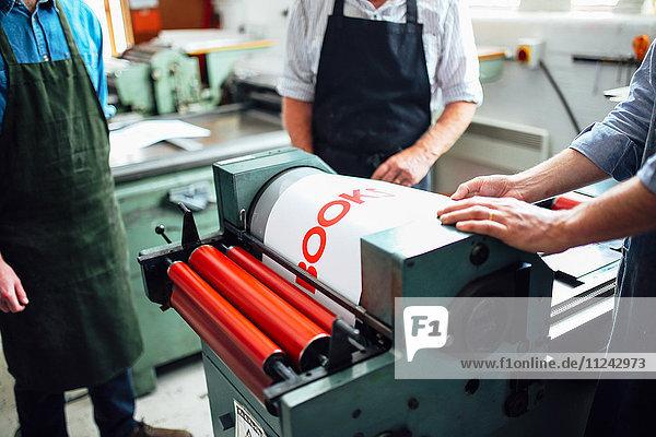 Handwerkern wird in einem Buchkunst-Workshop gezeigt  wie man die Buchdruckmaschine benutzt  mittlerer Abschnitt