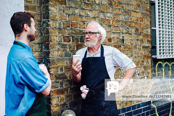 Älterer Handwerker trinkt Kaffee und unterhält sich mit einem jungen Mann außerhalb der Werkstatt