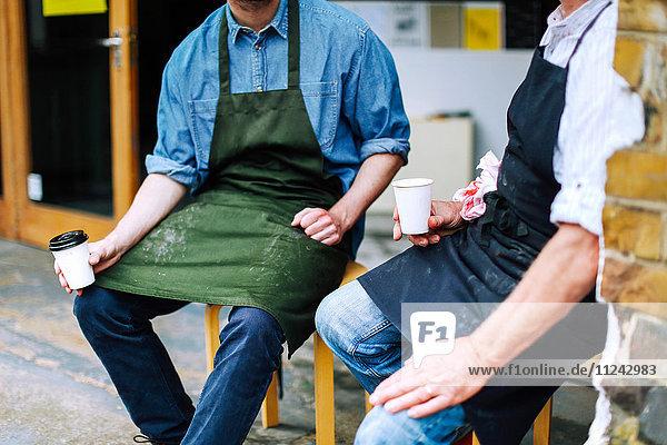 Älterer Handwerker trinkt Kaffee und unterhält sich mit einem jungen Mann außerhalb der Werkstatt  mittlerer Abschnitt