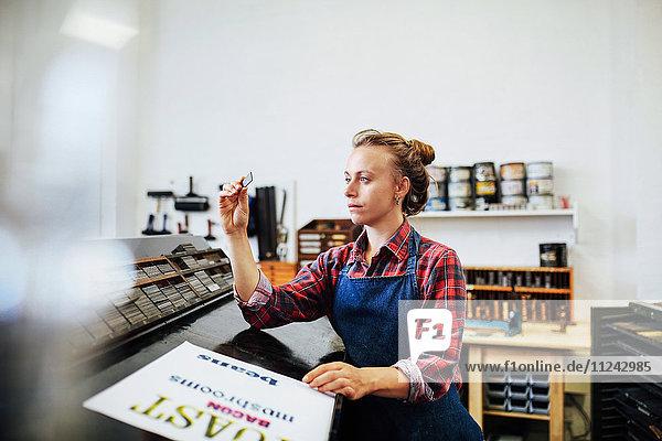 Junge Handwerkerin betrachtet in einem Buchkunst-Workshop die Abstände von Metallbuchdrucken