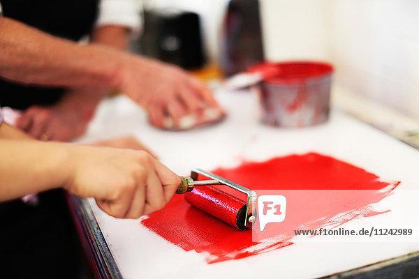 Nahaufnahme der Hände mit Farbwalze für den Buchdruck in einer Buchkunstwerkstatt