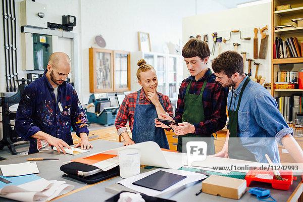 Gruppe junger Handwerker mit digitalem Tablett in einem Buchkunst-Workshop