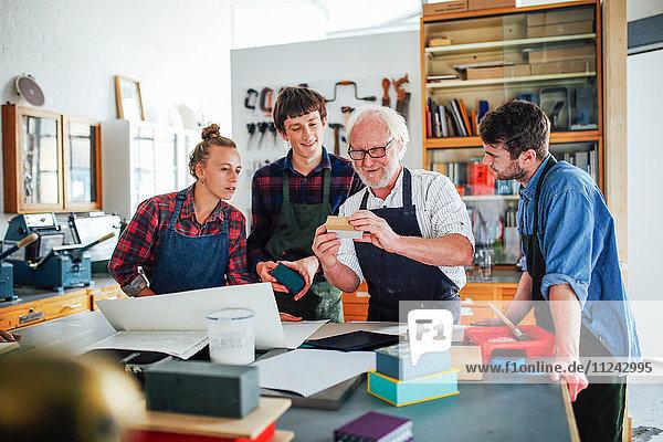Älterer männlicher Workshopleiter zeigt einer jungen Gruppe von Männern und Frauen in einem Buchkunst-Workshop Materialien