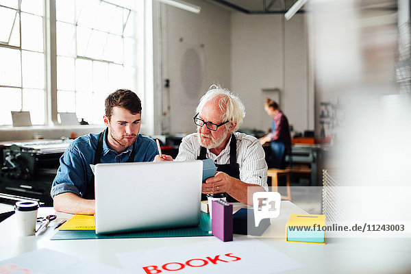 Älterer männlicher Handwerker und junger Mann schauen auf Laptop in Buchkunst-Workshop