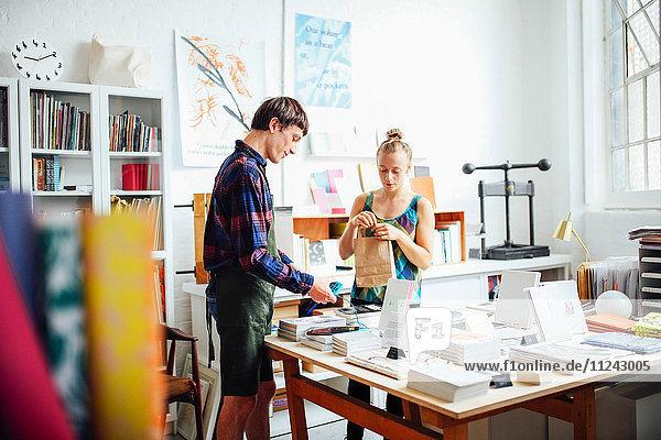 Junge Frau kauft Buch von jungem Handwerker in Kunstbuchhandlung