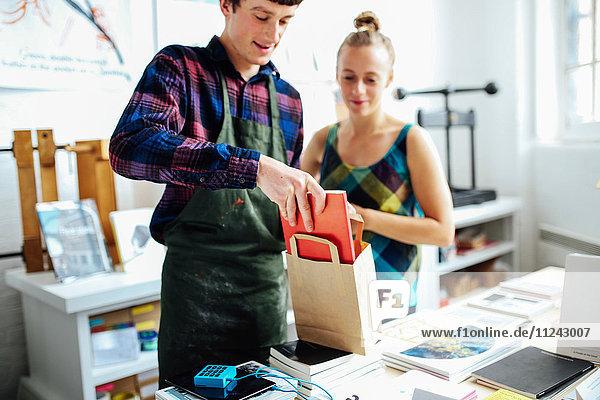 Junger Handwerker mit Kunde  der im Kunstbuchladen das Buch in die Tasche steckt