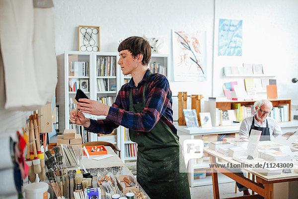 Junger Handwerker nimmt Pinsel in die Hand und betrachtet Materialien im Handwerksladen  mit einem älteren Mann im Hintergrund