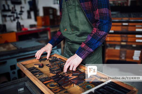 Ausschnitt eines jungen Handwerkers  der in der Druckwerkstatt durch ein Tablett mit hölzernen Hochdruckbuchstaben blickt