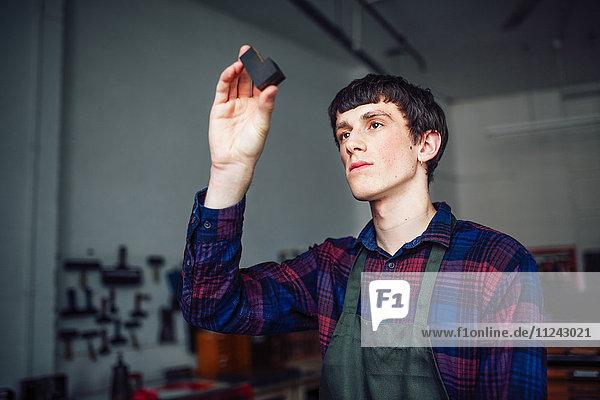 Junger Handwerker hält Buchdruckbuchstaben in Druckwerkstatt hoch