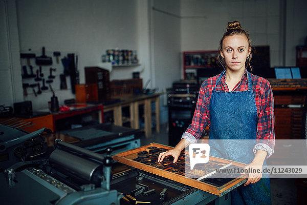 Porträt einer jungen Handwerkerin neben einem Tablett mit Buchdruckbuchstaben in der Druckwerkstatt