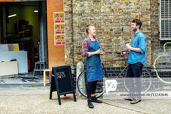 Junge Handwerkerin vor der Werkstatt  lacht und unterhält sich mit einem jungen Mann mit Schiebefahrrad