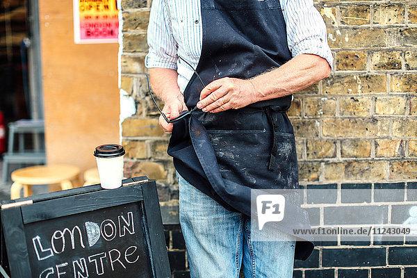 Leitender Handwerker vor der Werkstatt  putzt Gläser mit seiner Schürze  Mittelteil