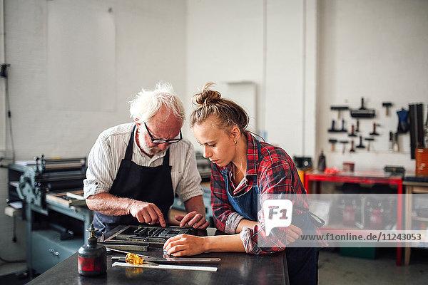 Senior-Handwerker arbeitet am Buchdruck mit einer jungen Handwerkerin in einer Druckwerkstatt