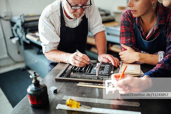 Älterer Handwerker benutzt Buchdruckausrüstung und unterrichtet junge Handwerker und Handwerkerinnen in einer Druckwerkstatt