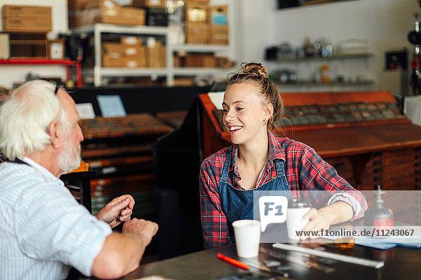 Junge Handwerkerin trinkt Kaffee  plaudert und lacht mit einem älteren Handwerker in einem Buchkunst-Workshop
