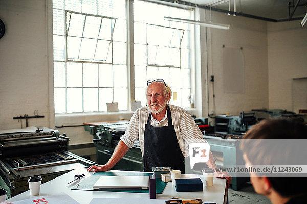 Leitender Handwerker/Techniker leitet Werkstatt im Buchdruckstudio