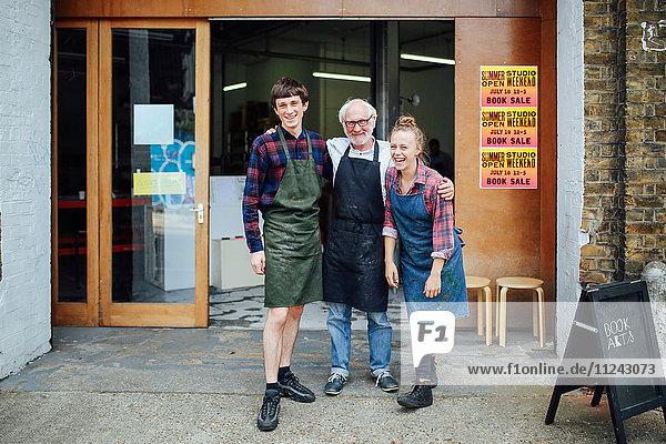 Familienporträt eines älteren Handwerkers mit Tochter und Sohn vor der Druckwerkstatt