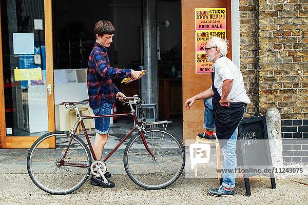 Junger Mann mit Fahrrad schaut auf Posten und steht mit einem älteren Handwerker vor der Druckerei