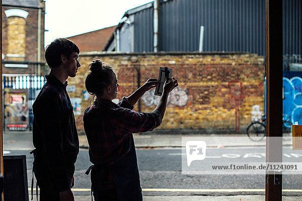 Silhouette eines jungen Handwerkers und einer jungen Handwerkerin  die ihre Arbeit aufhalten