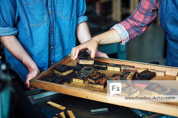 Junger Handwerker und Handwerkerin beim Betrachten von Briefen im Buchdruckatelier  Mittelteil