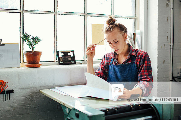 Junge Handwerkerin am Fenster  die sich an Buchdruckmaschinen lehnt und im Buchkunstatelier Papierarbeiten betrachtet