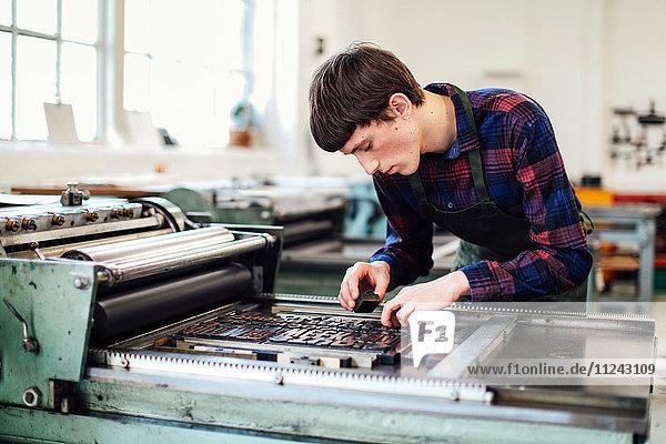Junger Mann arbeitet an einer Buchdruckmaschine in einem Buchkunst-Workshop