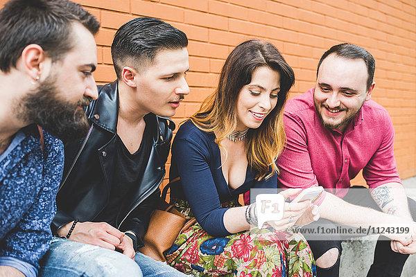 Gruppe von Freunden  die sich die Nachricht auf dem Handy ansehen.