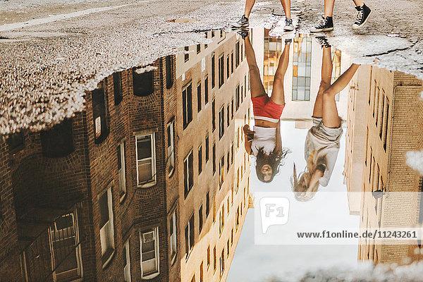 Frauen gehen auf der Straße durch eine Pfütze  Boston  MA  USA