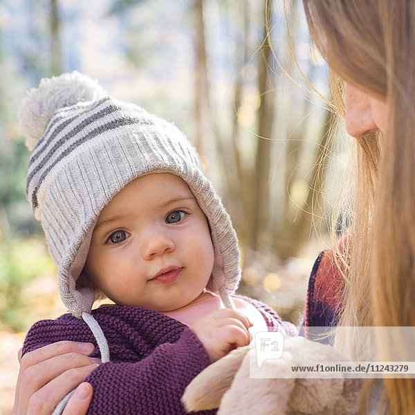 Portrait of baby girl wearing knit hat looking at camera