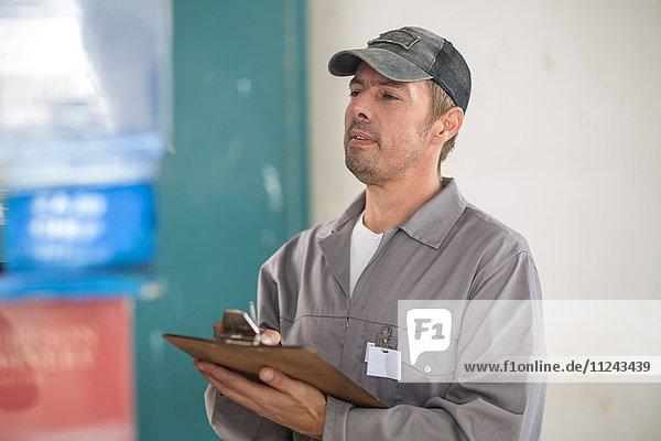 Werksleiter mit Zwischenablage zur Palettenkontrolle in der Verpackungsfabrik