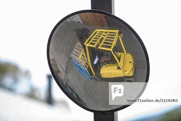 Konvexes Spiegelbild eines Gabelstaplerfahrers in einer Verpackungsfabrik
