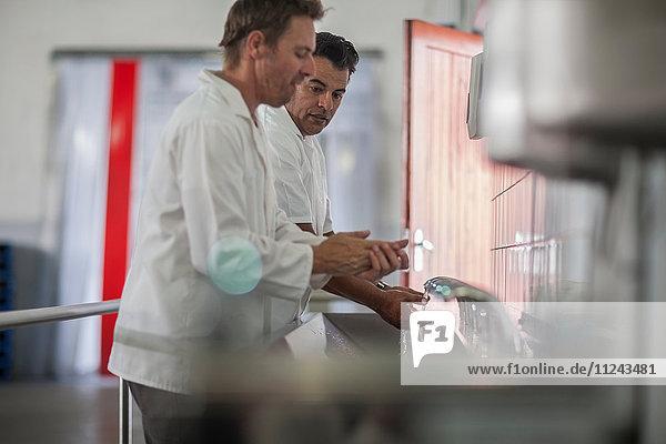 Zwei männliche Fabrikarbeiter waschen sich in Verpackungsfabrik die Hände