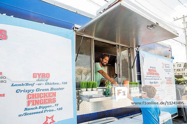 Mann im Fastfood-Anhänger  der einen Jungen durch die Luke serviert