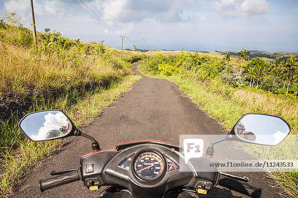 Mirror image of motorcyclist in motorcycle wing mirrors on rural road  Tanglad  Nusa Penida  Indonesia