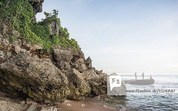 Three men on coastal rock at Panawa Beach  Bali  Indonesia